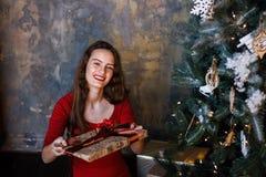 Усмехаясь маленькая девочка в красном платье с настоящими моментами и подарочными коробками под рождественской елкой стоковая фотография