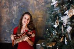 Усмехаясь маленькая девочка в красном платье с настоящими моментами и подарочными коробками под рождественской елкой стоковое фото