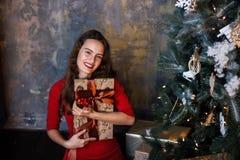 Усмехаясь маленькая девочка в красном платье с настоящими моментами и подарочными коробками под рождественской елкой стоковое фото rf