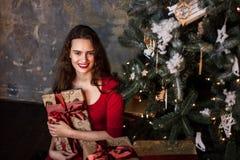 Усмехаясь маленькая девочка в красном платье с настоящими моментами и подарочными коробками под рождественской елкой стоковое изображение