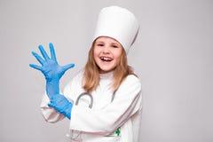 Усмехаясь маленькая девочка в медицинских равномерных и голубых перчатках Стоковое Изображение RF