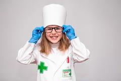 Усмехаясь маленькая девочка в медицинских равномерных и голубых перчатках Стоковое Фото