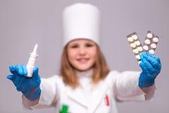 Усмехаясь маленькая девочка в медицинской форме держа носовой брызг и пилюльки для здоровья Стоковое Изображение