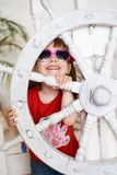 Усмехаясь маленькая девочка в солнечных очках с рулевым колесом Стоковое Фото