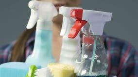 Усмехаясь маленькая девочка держа химикаты и щетки, качество уборки акции видеоматериалы