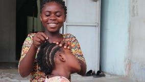 Усмехаясь маленькая девочка заплетает ее сестру видеоматериал
