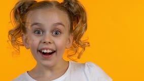 Усмехаясь маленькая девочка имея глаза потехи закрывая с в форме сердц детством леденца на палочке сток-видео