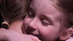 Усмехаясь маленькая девочка обнимая мать, нежные отношения в семье, любовь и заботу акции видеоматериалы