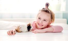 Усмехаясь маленькая девочка обнимая морскую свинку Стоковое Изображение