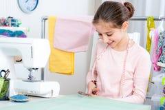 Усмехаясь маленькая девочка работая на швейной машине стоковое изображение rf