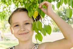 Усмехаясь маленькая девочка с ветвью дерева в одном портрете руки Красота, зеленый цвет, природа влюбленности Стоковые Изображения RF