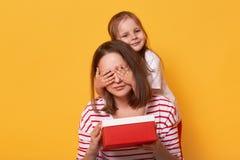 Усмехаясь маленькая дочь закрывает глаза к ее маме и дает ее красную коробку, представляет на День матери, сюрприз для мумии, сид стоковое изображение rf