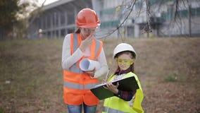 2 усмехаясь маленьких построителя планируя с жидкостным уровнем и светокопией акции видеоматериалы
