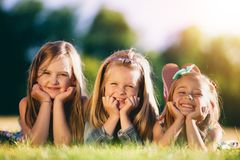 3 усмехаясь маленькой девочки кладя на траву в парке Стоковое Изображение RF
