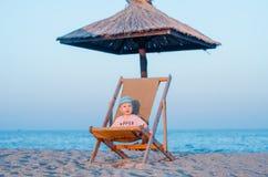Усмехаясь малый мальчик сидя в sunbed, lounger около моря и песок на заходе солнца лето seashells песка рамки принципиальной схем стоковые фотографии rf