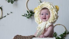Усмехаясь малыш в головном уборе сидит в деревянных представлениях на камере на крупном плане photoshoot видеоматериал