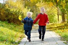 2 усмехаясь мальчика, который побежали через парк осени Стоковые Изображения