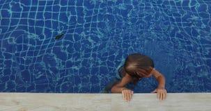 Усмехаясь мальчик в воде около края бассейна видеоматериал