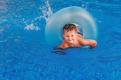 Усмехаясь мальчик плавает в голубом бассейне стоковое изображение rf