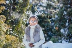 Усмехаясь мальчик с смешными antlers оленя Принципиальная схема праздника стоковое изображение