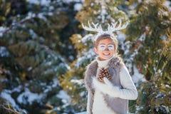 Усмехаясь мальчик с смешными antlers оленя Принципиальная схема праздника стоковые изображения
