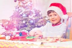 Усмехаясь мальчик украшая бумажную рождественскую елку стоковая фотография