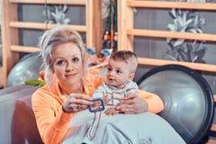 Усмехаясь мама ждет доктора для ее маленького малыша на шкафе педиатра стоковые изображения rf