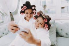 Усмехаясь мама при дочь делая Selfie в салоне стоковое фото rf