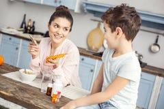 Усмехаясь мать говоря о витаминах с ее дорогим сыном стоковые фото