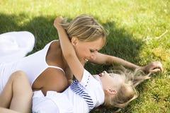 Усмехаясь мать и маленькая дочь на природе. Счастливые люди outdoors Стоковая Фотография RF