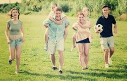Усмехаясь мать и отец с 4 детьми на зеленой лужайке Стоковое Фото