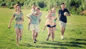 Усмехаясь мать и отец с 4 детьми на зеленой лужайке Стоковая Фотография RF