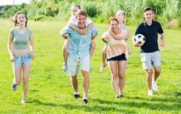 Усмехаясь мать и отец с 4 детьми на зеленой лужайке Стоковое Изображение