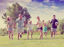 Усмехаясь мать и отец с 4 детьми на зеленой лужайке Стоковые Изображения