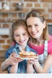 Усмехаясь мать и дочь держа плиту с пирожными Стоковая Фотография RF