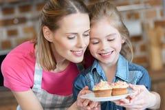 Усмехаясь мать и дочь держа плиту с пирожными Стоковые Изображения RF