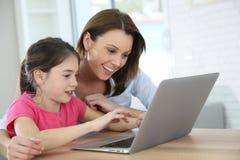 Усмехаясь мать и дочь играя на компьтер-книжке Стоковые Фото