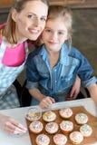 Усмехаясь мать и дочь с пирожными на борту Стоковые Изображения