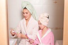 Усмехаясь мать и дочь чистя их зубы щеткой Стоковые Фото
