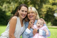 Усмехаясь мать сидя с бабушкой и ребенком Стоковые Изображения RF