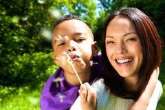 Усмехаясь мать с одуванчиком сына дуя Стоковое фото RF
