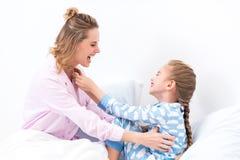 усмехаясь мать щекоча счастливую дочь на кровати стоковые фото