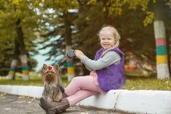 Усмехаясь маленькая белокурая девушка представляя с милым щенком Стоковая Фотография