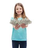 Усмехаясь маленькая девочка давая деньги наличных денег доллара стоковые изображения rf