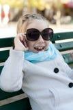 Усмехаясь маленькая девочка в говорить на сотовом телефоне стоковые фото