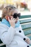 Усмехаясь маленькая девочка в говорить на сотовом телефоне стоковые изображения