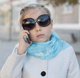 Усмехаясь маленькая девочка в говорить на сотовом телефоне стоковая фотография rf
