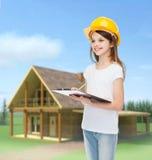 Усмехаясь маленькая девочка в защитном шлеме с доской сзажимом для бумаги Стоковое Изображение RF