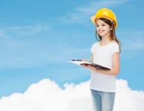 Усмехаясь маленькая девочка в защитном шлеме с доской сзажимом для бумаги Стоковое Изображение