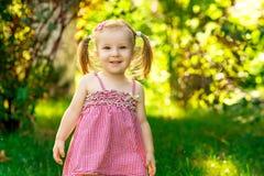 Усмехаясь маленькая девочка в луге в парке Стоковое Изображение RF